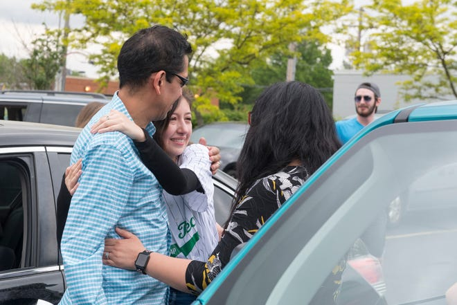 Mario Vazquez, left, and his wife Manoela, right, hugs their daughter Addison Johnson, center, after a group of 12 students of the Associate Accelerated Program (ASAP) celebrated their completion of an associate's degrees in just 11 months at Ivy Tech in Evansville, Ind., Friday afternoon, May 15, 2020. This was the sixth cohort to complete the program but the class of 2020 had to overcome unprecedented hurdles, including finishing the last eight weeks of their schooling remotely due to the COVID-19 pandemic.  Johnson graduated with honors and was named outstanding graduate of the School of Art, Science, and Education at Ivy Tech.