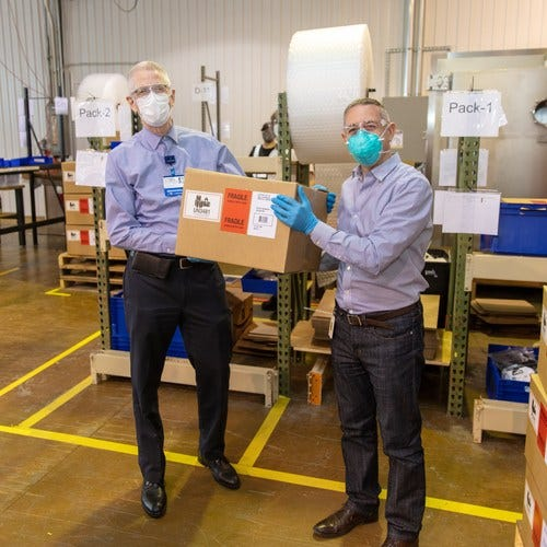 Dr. John Froggatt III, left, of Spectrum Health Lakeland in St. Joseph Michigan, receives the first box of PAPR units donated by Whirlpool Corporation, Dow, and Reynolds Consumer Products from Christian Gianni, President of WIN Health Labs and VP of Technology for Whirlpool Corporation. Froggatt is an infectious disease specialist in Saint Joseph, Michigan, and has been practicing for 31 years.