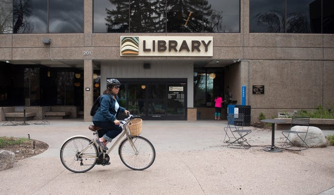 Patrons return books to the Old Town Library as Poudre River Public Library District reopens drop boxes for book returns in Fort Collins, Colo. on Friday, May 15, 2020.
