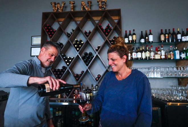 Mark Hrubesky pours his wife, Beth, a glass of wine on Thursday at their restaurant, Studio 1212 Cafe & Wine Bar, 1212 Marine St., Green Bay. The Hrubeskys are hoping to open their doors for dine-in when the stay-at-home order expires on May 20.