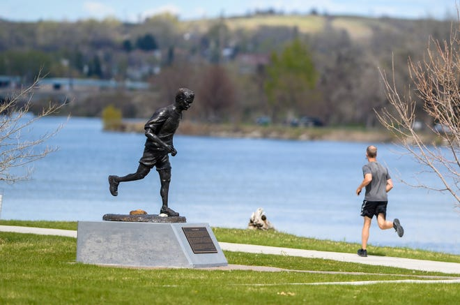 A runner runs past the Branch Brady sculpture in West Bank Park Thursday. Rain is expected across northcentral Montana through Thursday.