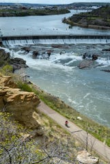 A cyclist rides the River's Edge Trail near the Missouri River's Black Eagle Dam in Great Falls Thursday. Missouri River tributaries such as the Sun River could see an influx of snowmelt this week as rains are expected across the region through Thursday.