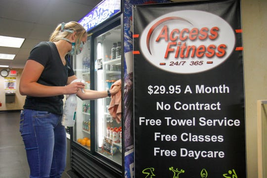 Kaelyn Frahm, who has worked at Access Fitness since January, sanitizes surfaces at the gym on Friday, May 15. Friday was the first day that gyms were able to open in Montana after Gov. Steve Bullock included gyms, theaters and museums to open in phase one in the state's phased reopening approach.