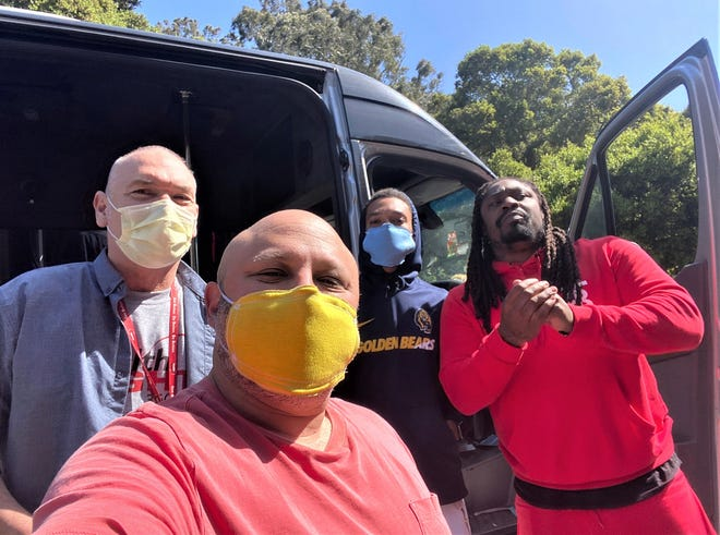 Jeremy Castro (front) and Marshawn Lynch pause for a selfie while delivering masks.
