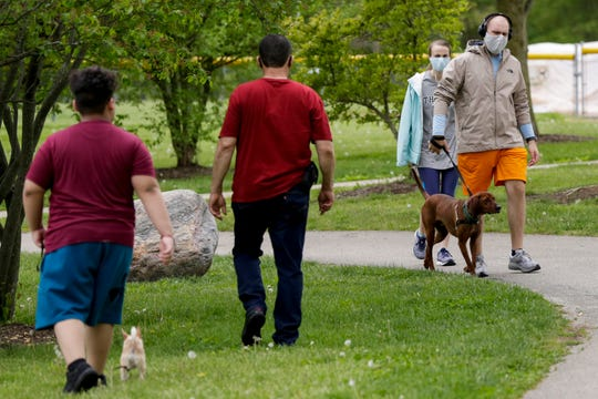 Park goers walk their dogs around Armstrong Park, Friday, May 15, 2020 in Lafayette.