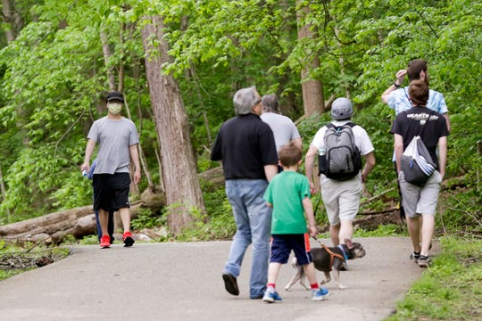 A lone walker wears a mask while walking along the Wabash Heritage Trail in Happy Hollow Park, Friday, May 15, 2020 in West Lafayette.