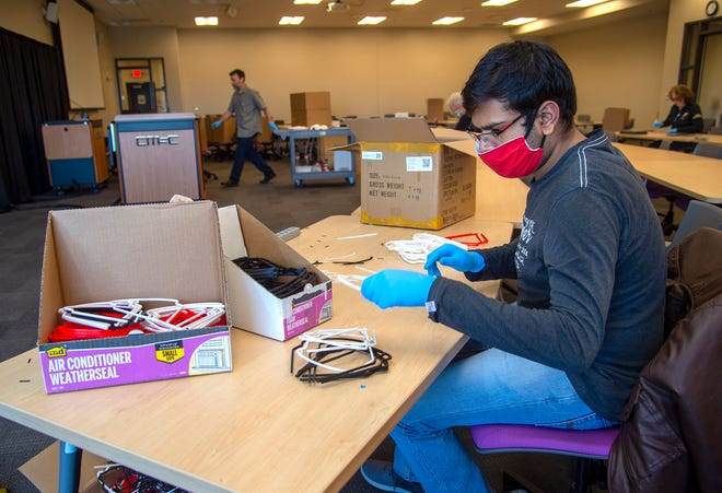 Mechanical Engineering graduate student Kshitiz Gupta inspects frames for face shields prior to assembly.