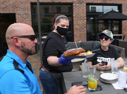 """""""I'm so happy to be back at work,"""" said server Meghan Hunter. She attends to customers sitting out in the patio area at The Exchange Pub + Kitchen in the New Albany. Employees of the restaurant have their temperature checked before the enter the restaurant as well as once during their shift in an effort to prevent Covid-19. Wearing a mask at times """"feels like I'm being smothered with a pillow,"""" Hunter said, but understands the """"new normal."""" May 14, 2020"""