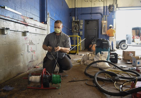 Sparrow Health System team electrician Tod Davis works at the former Sears Automotive Center located in Frandor Shopping Center, Friday, May 15, 2020. The former auto-repair bays will be turned into drive-thru COVID-19 testing sites.