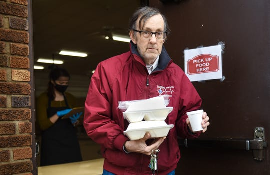 Jon Vogler of Lansing picks up hot meals and coffee for he and his wife Friday, May 15, 2020, at Cristo Rey Community Center in Lansing.  The non-profit has had to close their dining room due to COVID-19, but hot meals are still available at their makeshift pickup window.
