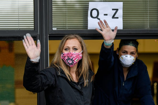 First grade teacher Lindsay Swain, left, and reading interventionist Stephanie Lampi waves to families at Marble Elementary School on Friday, May 15, 2020, in East Lansing. Parents dropped off books and picked up student belongings in the front of the school.