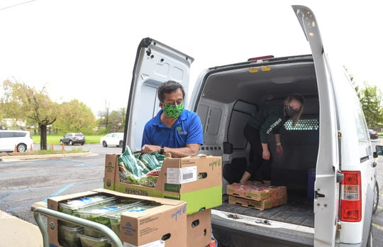 Cristo Rey Community Center Executive Director Joe Garcia and food access worker Kelsey Black unload a delivery of fresh fruit and vegetables Friday, May 15, 2020, for the non-profit's food pantry.