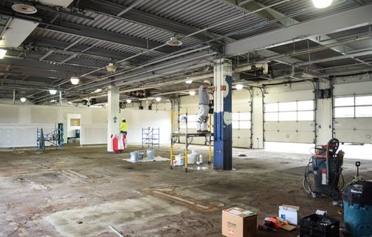 Painters and drywallers work at the former Sears Automotive Center located in Frandor Shopping Center, Friday, May 15, 2020. The former auto-repair bays will be turned into Sparrow Health System drive-thru COVID-19 testing sites.