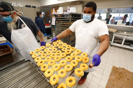 Larico Brown carries a tray of fresh donuts as Gibson's reopens Friday, May 15, 2020 after being closed for two months during the economic shutdown of the city caused by the coronavirus pandemic.