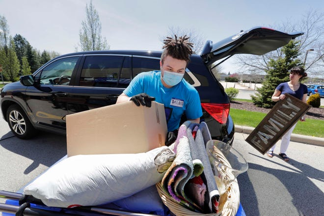 Dalano Jordan, an employee at Goodwill in Brookfield, unloads bags of donated items as Goodwill stores reopened Friday.