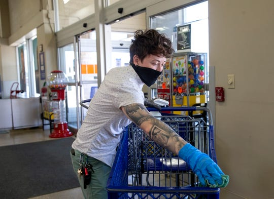 Assistant store manager Jae Reuter cleans a shopping cart in a Goodwill store Friday in Waukesha. After customers dropped off shopping carts, Goodwill employees have to clean and sanitize them before putting them back to use.