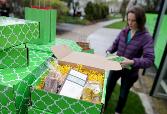 Theresa Nemetz, founder and chief experience officer of Milwaukee Food & City Tours, organizes care packages on Thursday. Milwaukee Food & City Tours can't load up buses of strangers to take them on a tour of Milwaukee, so it's created care packages with local items that can be delivered to customers' doors.
