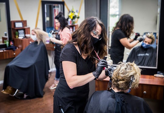 Kimberly Sherwood styles a client's hair at Twisted Scissors on McGalliard Road Thursday, May 15, 2020. Sherwood said she's been working 12-14 hour days and has fifty clients her first week back from COVID-19 closure.