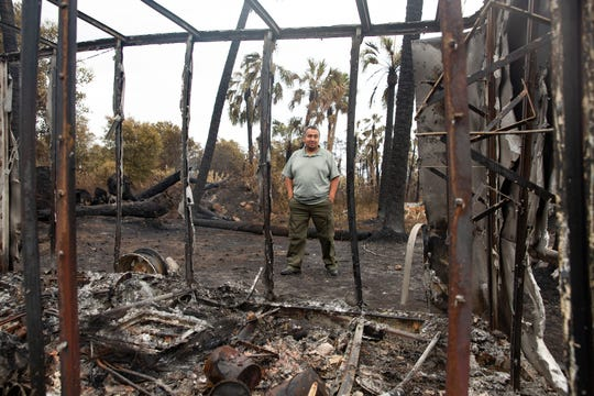 Guillermo Meza looks over the remains of his trailer during a tour of his property, Friday, May 15, 2020, in Golden Gate Estates.