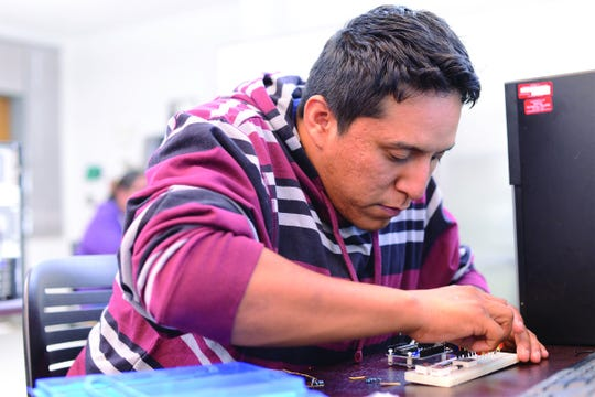 Navajo Technical University student Cyrus Leopold Norcross tinkers with an LED light project in the school's Electrical Engineering Fundamentals I course in 2015. NTU received a National Science Foundation grant this month to expand its engineering department.