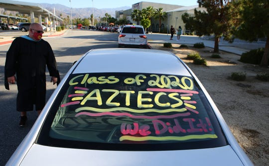 Palm Desert High School Principal Dennis Zink greets seniors during a drive-thru caps and gown ceremony at the school in Palm Desert, Calif., on May 14, 2020.