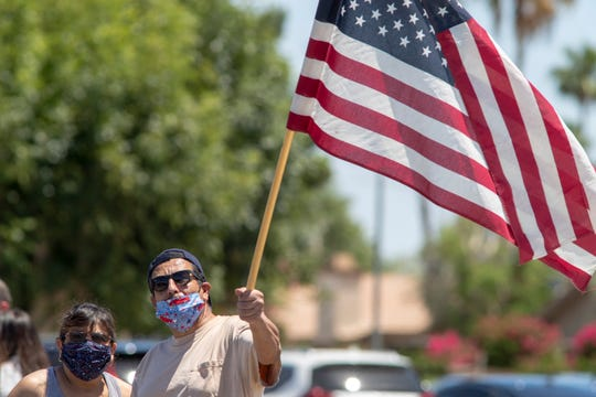 Genny Gonzalez and Pablo Gonzalez of Indio wait for vintage aircraft fly over JFK Memorial Hospital in Indio, Calif., on May 15, 2020. The Palm Springs Air Museum has scheduled fly overs every Friday in May as a way to honor health care workers and first responders during the COVID-19 pandemic.