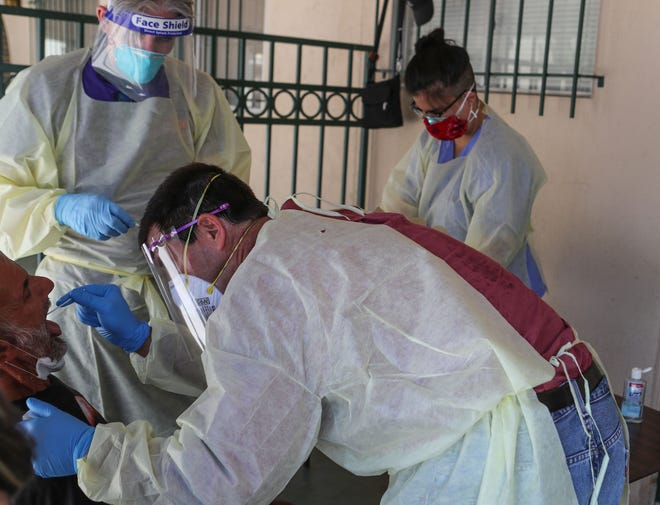 Dr. Richard Loftus, bottom, administers a coronavirus test to an individual Our Lady of Guadalupe Church in Palm Springs, May 15, 2020.  The Coachella Valley Volunteers in Medicine tested homeless individuals.