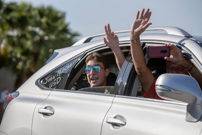 Palm Desert High School senior John Mitchell, left, and Hank Colman wave to teachers after Mitchell received his cap and gown in a drive-thru ceremony at the school in Palm Desert, Calif., on May 14, 2020.