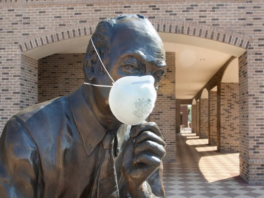 The bronze statue of J. Earle Bowden wears a mask during the coronavirus pandemic in downtown Penscola on Thursday, March 26, 2020.