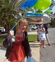Gulf Breeze High School senior Allison Linkous reacts after a drive-by parade outside of her home Friday celebrating her winning a full-ride scholarship to the University of West Florida.