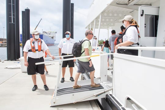 Craig Pearson, center, and other passengers board the Pelican Perch ferry at the Pensacola Terminal as Pensacola Bay Cruises resumes service in Pensacola on Friday, May 15, 2020.