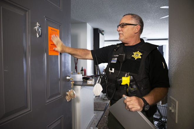 On May 15, 2020, Constable David Lester serves an eviction notice at an apartment in east Phoenix.