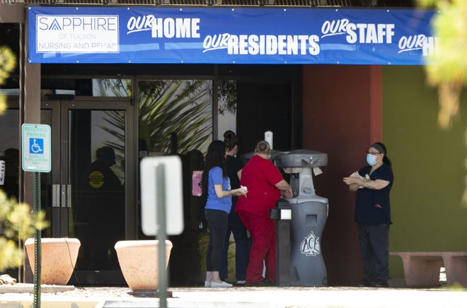 People wash their hands by the entrance to Sapphire of Tucson Nursing and Rehabilitation on May 1, 2020.