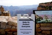 A social distancing sign is seen at the Grand Canyon Friday, May 15, 2020. Tourists are once again roaming portions ofGrand Canyon National Park when it partially reopened Friday morning, despite objections that the action could exacerbate the coronavirus pandemic.