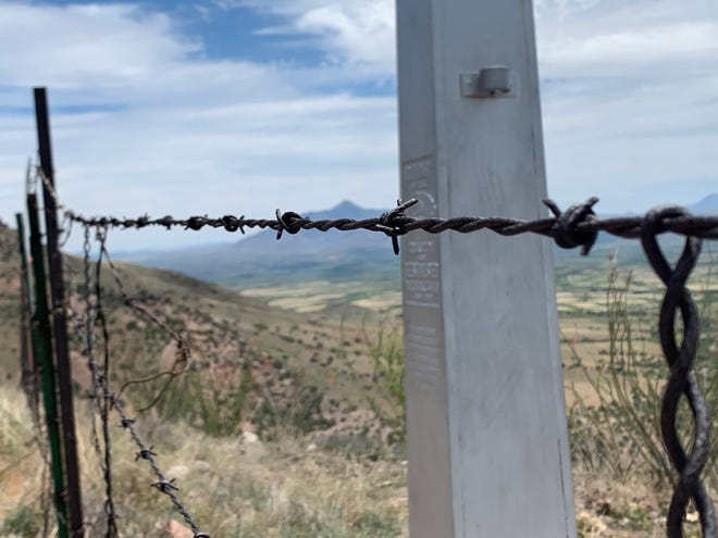 Barbed wire and a historic monument delineates the U.S.-Mexico border through the Huachuca Mountains in southern Arizona. Border officials plan on replacing it with 30-foot bollards.
