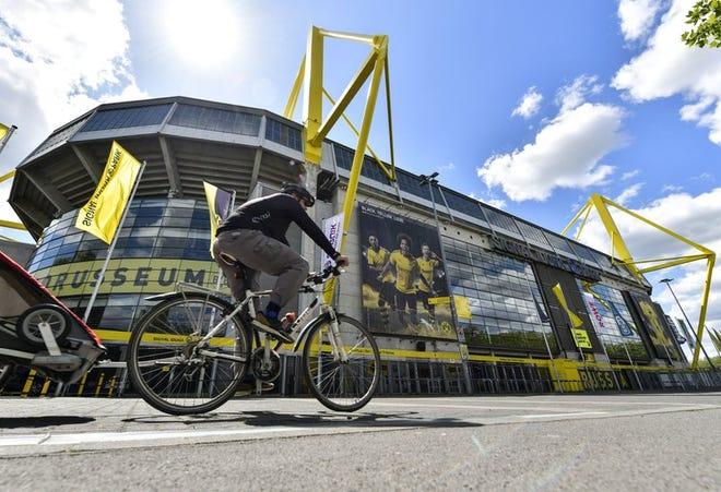 Un hombre pasea en bicicleta frente al Signal Iduna Park, el estadio más grande de Alemania y hogar del Borussia Dortmund, en Dortmund, Alemania, el jueves 14 de mayo de 2020.