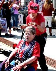Using a borrowed knife, Bridget Nowak gives an impromptu haircut to Elizabeth Castelli of Shippensburg during a Reopen PA rally in Harrisburg Friday, May 15, 2020. Nowak works as a stylist at a salon in Bethel Park. About one thousand protesters participated at the rally in front of the capitol building. Bill Kalina photo