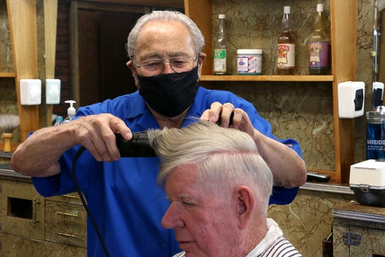 Longtime local barber Enzo Buonamici gives a haircut to Albert Bylund in his shop, the Village Barber Shop, in Reno on May 14, 2020. Buonamici, who is 89 years old, is retiring and closing his shop on the 19th of this month.