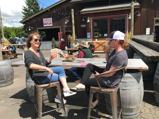 Kelly Smith (left) and Wendy Henderlong (right) enjoy palomas in the sunshine at Grain Station Brew Works in McMinnville on Friday, May 15, 2020. Unlike Marion and Polk Counties, restaurants in Yamhill C ounty were approved to resume on-premises dining.