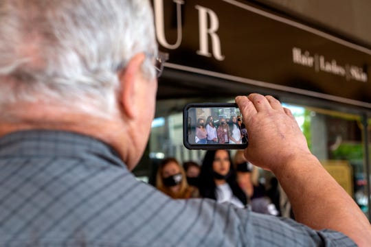 A supporter of Lindsey Graham films the press conference she called at Glamour Salon in downtown Salem on May 15, 2020.