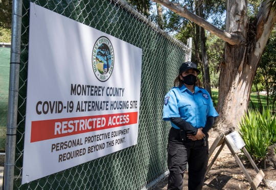 A Condor Security of America guard stands next to a Monterey County COVID-19 alternate housing site sign at San Lorenzo Park in King City, Calif, on Thursday, May 14, 2020.