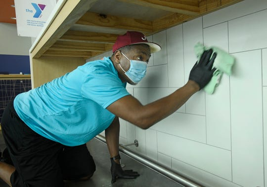 Willie Heggler cleans the Shreveport YMCA before it reopens to the public.