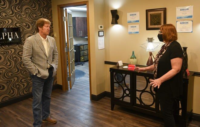 U.S. Senate candidate Jason Lewis speaks with Alpha Salon Lux Suites owner Sandy Svihel Friday, May 15, 2020, in St. Cloud.