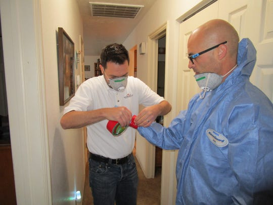 Jonathan Webb, left, helps Red Desert Decon technician Hyrum Taylor suit up before a cleanup project.