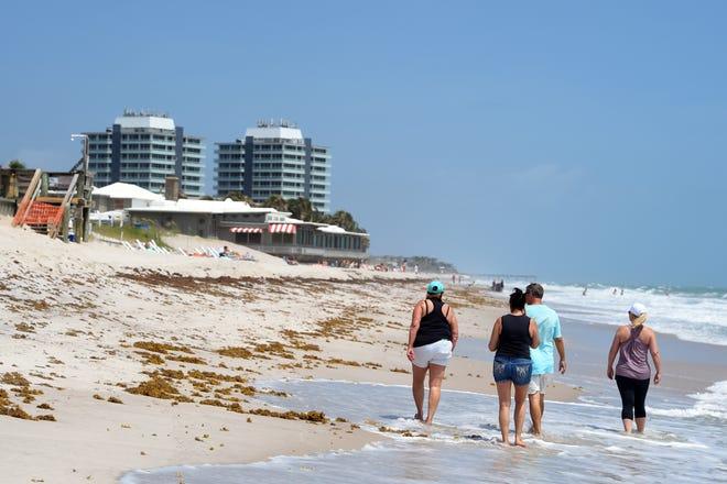 Beach-goers walk along the waterline on Friday, May 15, 2020, in front of Costa d'Este Beach Resort & Spa in Vero Beach.