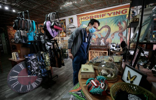 Roberto Stevens peruses Dreadful Things in northeast El Paso after their reopening. The store carries everything from the  macabre to original artwork by the store's owner Francella Salgado. The store was forced to close only two weeks after their grand opening in March.
