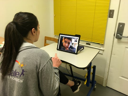 Occupational therapist Francine Sotirhos works with Michael Cajarmarca, 11, during a telehealth session. Cajarmarca has a brain tumor that causes weakness on his right side and affects his vision.