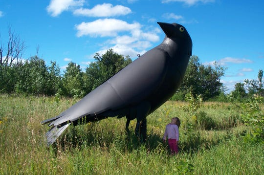 """The Three Crows"" are three larger-than-life birds sculptures crafted by artist Will Salisbury."