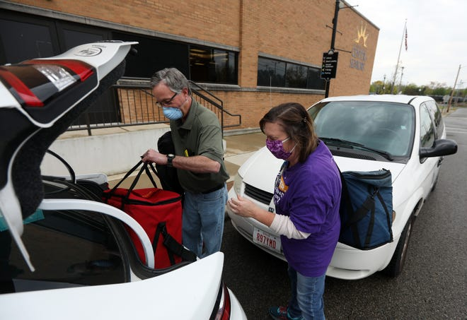 Tara Rock and John Brookover load meals into a vehicle before setting out to deliver meals to home-bound senior citizens recently. The Muskingum County Center for Seniors delivers more than 700 meals across the county every week day.