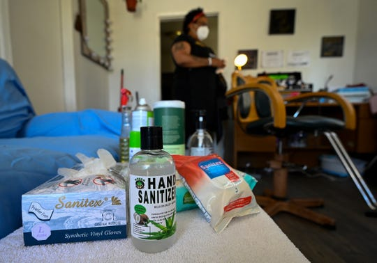Sanitizers and protective gloves sit on a table in Carmelle Harris's house as she waits for her next client.